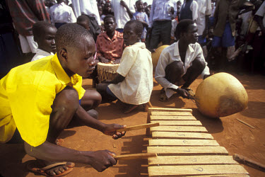 IDP (internally displaced person) children playing musical instruments made out of basic materials.