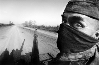 A Russian soldier advancing with his tank down an isolated road in the Chechen countryside.