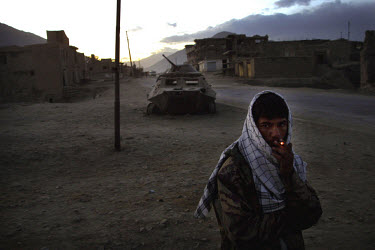 A Northern Alliance soldier stands guard outside a military base in Kabul. In the background sits a destroyed Russian Armoured Personnel Carrier.
