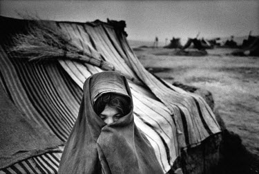 A young girl wrapped up against the cold in the refugee camp of Xjosa Sabz Poosh. 1100 families live in basic tents, and more than 200 people have died from hunger and cold over the past seven months....