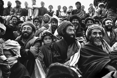 Excited faces in the crowd watching a game of Buzkashi, Afghanistan's national sport. Literally translated as ^goat grabbing^, it is played by two teams of men on horseback. They battle for control of...