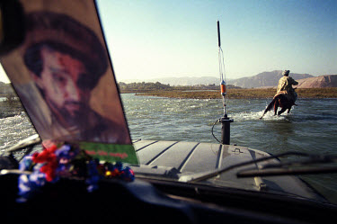 A man on horseback leads a four-wheel drive across the Kokcha River. The image of the late Ahmed Shah Massoud, icon of the Northern Alliance, is often used to signify kinship with the soldiers manning...