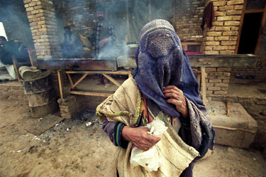 A woman wearing a burqa begs for money at a food stall. Forbidden from working by the Taliban, many women were forced into begging to support themselves and their families.