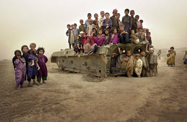 Children in Nawabad refugee camp sitting on a piece of abandoned military hardware. Across Afghanistan, the detritus of war has become a plaything for generations of children.