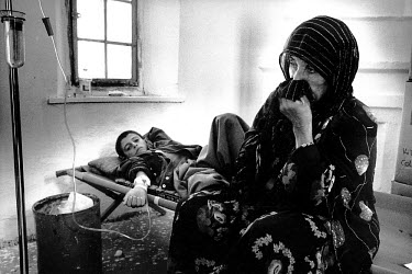 A Kurdish mother sits by her son�s hospital bed. They had just returned from Turkey to the designated United Nations Safe Haven in Northern Iraq. They arrived in their home town to find their homes de...