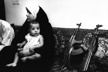 A woman sitting with her child in the headquarters of the armed forces of the Iraqi National Congress (INC). Moments later the compound was overrun by Iraqi agents. The INC is a coalition of all oppos...