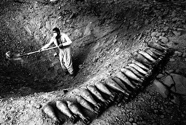 A worker from the Mines Advisory Group, a British-based NGO, prepares a pit for the destruction of mortar grenades. Millions of landmines and unexploded ordnance litter the former front line in the Ir...