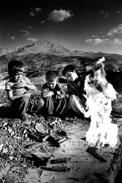 Dangerous games: Kurdish children break open ammunition and set fire to the gunpowder inside. Millions of landmines and unexploded ordnance litter the former front line in the Iran/Iraq war, still kil...