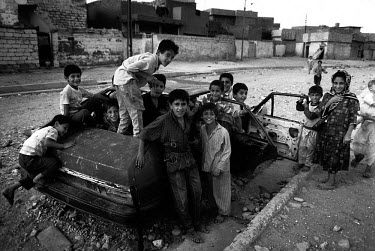 Children play in a car wreck on the outskirts of Erbil. Due to the United Nations embargo against Iraq and an Iraqi blockade against Kurdistan, the economic situation in the region was terrible. Kurdi...