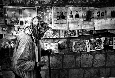 A beggar walks past a newspaper stand. Due to the United Nations embargo against Iraq and an Iraqi blockade against Kurdistan, the economic situation in the region was terrible. Kurdistan.