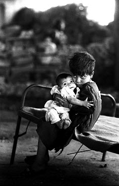 A Kurdish child looking after a baby after they fled from fighting in Halabja. Factions including the Islamic Movement of Kurdistan (IMK) and the Patriotic Union of Kurdistan (PUK) had been battling f...