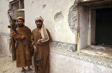 Anti-Taliban fighters outside the home of Mullah Mohammed Omar, spiritual leader of the Taliban. The building was damaged by US bombs on the first night of the air strikes in October, although it was...