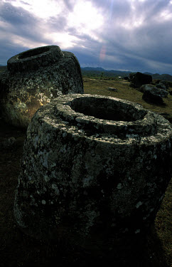 Dawn breaks over the unexplained mystery of the Plain of Jars, 2000 year old giant stone urns which litter the landscape at several sites on the central northern plateau of Laos.