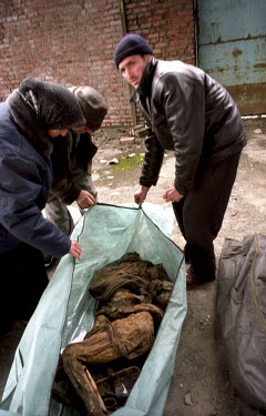 Chechens searching for missing relatives unzip bodybags holding unidentified remains found in a mass grave. In February 2001 Russia authorities disclosed the location of the grave in the grounds of th...