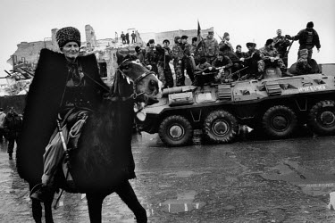 A Chechen man wearing traditional clothing rides his horse in front of a Russian tank captured by Chechen forces when the Russians withdrew from the city.