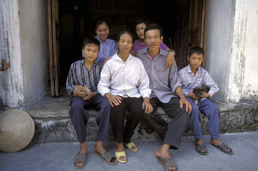 Family outside their home in Nam Ha village.