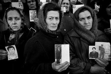 Chechen women holding photographs of their sons and husbands during a gathering of women searching for arrested and missing male relatives.