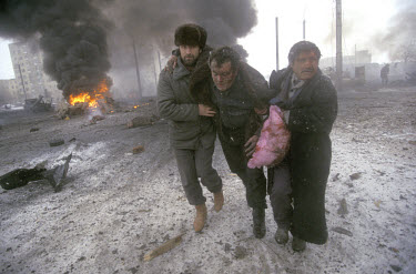 A wounded civilian is helped to safety after a Russian bombing attack which killed 18 people, including the American photographer Cynthia Elbaum.~In December 1994 Russian troops entered Chechnya in an...