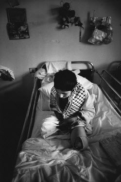 A Palestinian boy recovers from the amputation of a hand and both legs after an Israeli settler had thrown a grenade into his home.