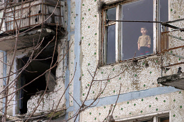 A young boy looks out the window of a flat in central Grozny. Bullet holes riddle the facade and the next flat has a gaping hole, a testament to the fierce fighting that occurred here.