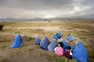 The Shomali Plains, north of Kabul. Women in burqas huddle with their children as they wait for transport to the capital.
