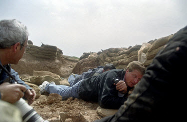 Julian Manyon, a reporter with the British TV company ITN, takes cover during an Iraqi mortar attack. He was travelling with Kurdish peshmerga fighters and US special forces who were attacking Iraqi p...