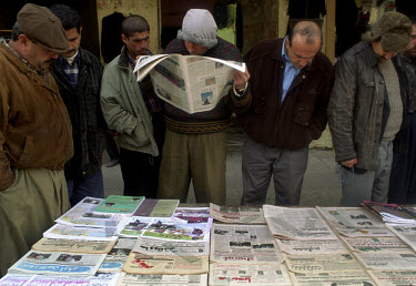 Kurdish men avidly read newspapers to find out the latest news in the build-up to the second Gulf war.