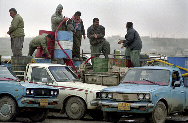 Kurdish petrol smugglers load fuel from one truck to another.