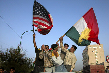 Kurdish youths wave the American and Kurdish flags to celebrate the fall of Baghdad that day. US and British troops invaded Iraq on 20th March with the aim of overthrowing the regime of Saddam Hussei...