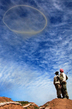 Peshmergas of the Kurdistan Democratic Party (KDP) watch a smoke ring in the sky after the demolition of UXO (unexploded ordnance) left behind by the fleeing Iraqi army, who abandoned their position t...