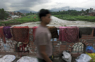 The Bagmati river at Thapathali in the height of the monsoon. The gushing rainwater brings a temporary respite from the noxious smells that emanate from the polluted river. The washing hanging on the...