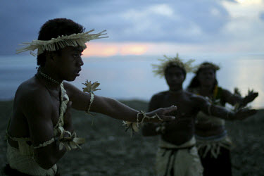 Men and women perform a traditional dance in Tarawa. Kiribati is a nation of 33 coral atolls scattered about the equator, inhabited by about 77,000 people. It is a society with little in the way of pa...
