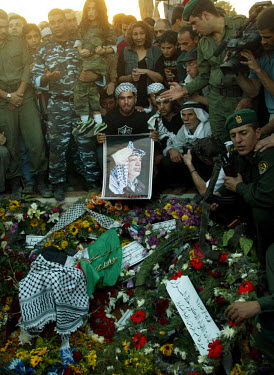 Emotional Palestinians gather around the grave of Yasser Arafat shortly after his burial.