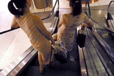 Two girls descend an escalator after a day's shopping.
