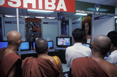 Monks watching scantily-clad women on TV at a trade exhibition.