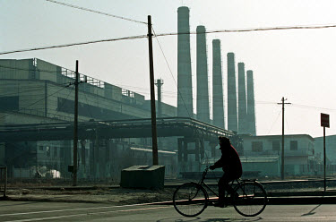 A cyclist pedals past smokestacks at the state-owned Baotou iron and steel works.