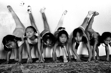 Girls at their daily lesson in contortion at the Mongolian State Circus. 'Flexible' children begin attending lessons at about five or six years of age, hoping to one day perform in the circus, earn a...
