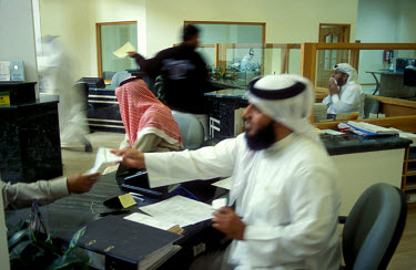 Doing business in the male clients' section of the Shamil Islamic Bank branch in central Manama. Banks in Bahrain operate a strict segregation policy whereby men and women bank in separate areas.