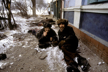 Two ethnic Russian men injured in an artillery attack. The man on the left had both his legs blown off. They had been standing in line at what they had heard was a distribution point for bread. Many R...