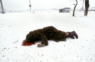 An elderly ethnic Russian woman lies dead on Grozny's snow covered streets after she was hit in an artillery attack. Many Russian residents of Grozny had no relatives in rural Chechnya where they coul...