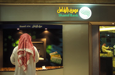 A customer of the Shamil Islamic Bank using a bank machine (ATM) in a shopping mall.