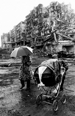 Chechen civilians walk with their belongings in a baby carriage out of the city after it was bombed and shelled by Russian forces during the invasion which began in December 1994.