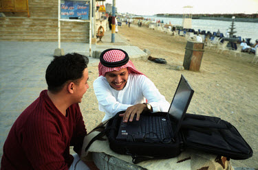Two men using the internet and a laptop computer on a beach on the Red Sea coast outside Jeddah.