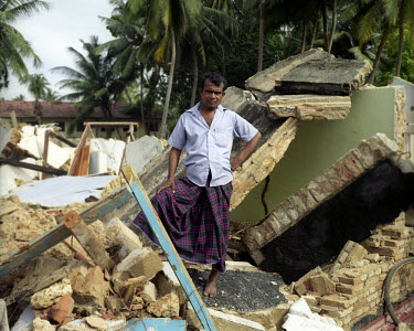 A man stands in the wreckage of his home, destroyed by the tsunami which struck South Asia on 26/12/2004. An underwater earthquake measuring 9 on the Richter scale triggered a series of tidal waves wh...