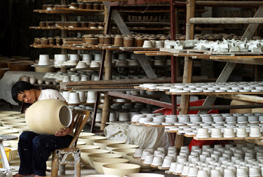 A worker puts the finishing touches to a clay vase at a porcelain workshop. The township of Jingdezhen has been known as China's porcelain capital since it was selected exactly one thousand years ago...
