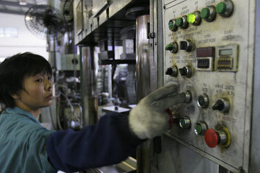 A worker operating a machine that makes metal trays at the Shanghai Xinpeng Industry factory.