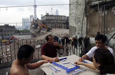 Residents play mahjong (mah jong) on the balcony of an old housing complex, across from the rubble of what used to be the Friendship Store in the Bund district. The city of Shanghai has started a rede...