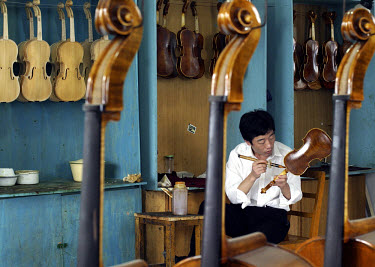 A craftsman lacquers a violin at the Shanghai Wellsound Tianyin violin factory. Founded by a family with four generations of expertise in the industry, the company exports most of its high-end and han...