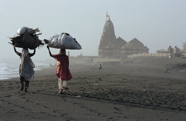 Women carrying a heavy load along the beach towards Somnath's Hindu temple. Dedicated to the God Shiva, the temple shelters one of the twelve sacred symbols of Shiva in India.