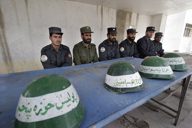 Police guards sit with their helmets at the entrance to a police compound.